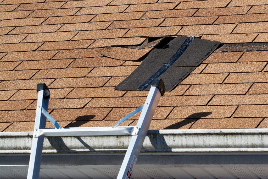 Roofing repair showing loose shingles